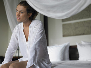Young Woman in Shirt Sitting on Bed