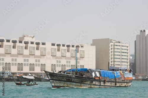 dubai uae a dhow an old wooden sailing vessel filled with cargo leaves the dock in deira.