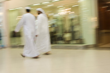 dubai uae two men traditionally dressed in dishdashs and gutras white robes and headdresses.