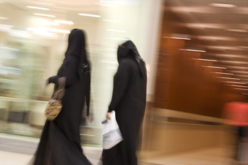dubai uae two women dressed in traditional abayas and hijabs black robes and scarves.