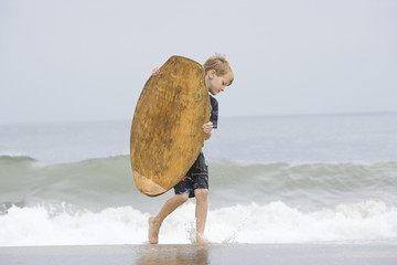 Little Boy Carrying a Bodyboard