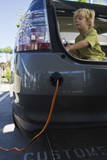 Boy 5-6 sitting in open car trunk at gas station