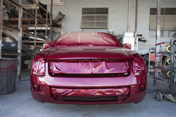 Front of red painted car in garage