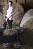 Girl shoveling hay in barn