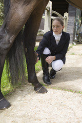 Girl grooming horse's leg, outdoors