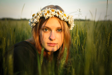 Beautiful young redheaded woman with flower diadem