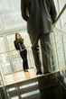 Businesswoman on cell phone and businessman walking down staircase