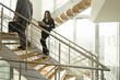 Businesswoman on staircase reading document and businessman walking up