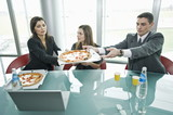Business people sharing pizza at desk