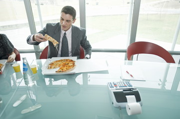 Business people eating pizza at desk