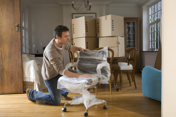 man unpacking chair in unfurnished room
