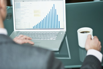 Businessman with coffee cup at laptop with bar chart