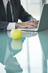 Businessman with apple at laptop