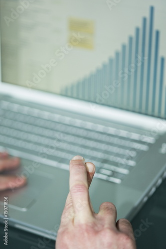 Businessman's fingers crossed at laptop with bar chart