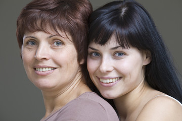 Studio portrait of young woman embracing mother