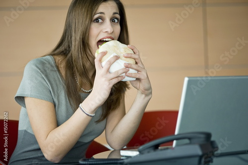 Businesswoman eating pita sandwich at desk