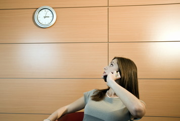 Businesswoman on telephone looking at clock
