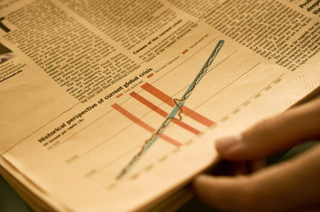 Hand holding newspaper with chart analyzing financial crisis