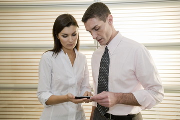 Businessman and businesswoman looking at calculator