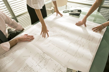 Closeup of professionals looking at architectural plans on desk