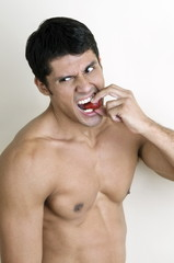 Fit young man biting a strawberry