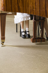 Low section of child and teacher at piano