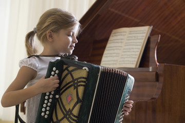 Girl 5-6 playing accordion