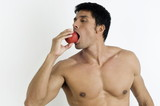 Fit young man biting an apple