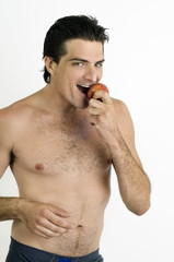 Young man biting an apple