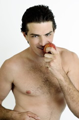 Young man holding an apple to his mouth