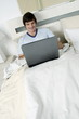 Young man in bed with laptop computer
