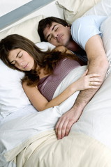 Young couple in bed sleeping