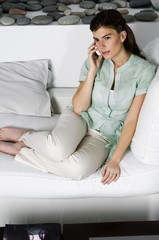 Young woman on couch talking on phone