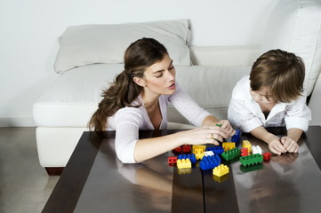 Young woman and boy playing with building blocks