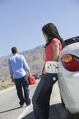 woman waiting for man to refuel car