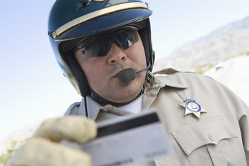 Highway patrol officer examines driving license