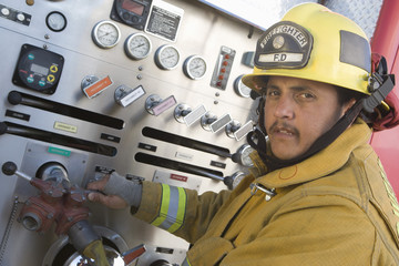 Firefighter at control panel of truck
