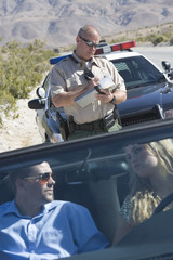 Police officer checks details of vehicle with couple driving