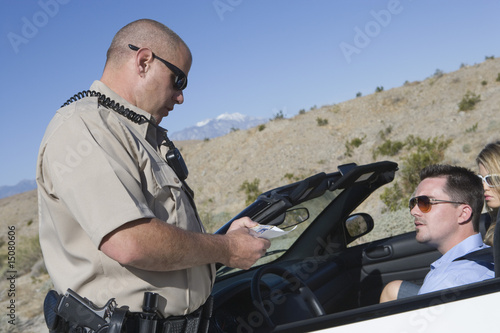 Police officer checking on driver in desert