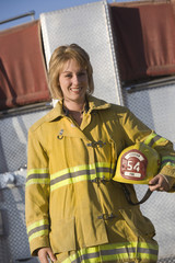 Portrait of female firefighter holding helmet