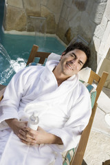 Portrait of man relaxing by swimming pool