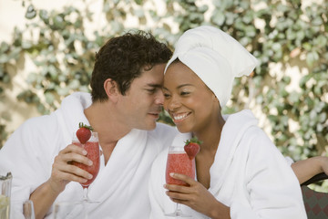 Couple in bathrobes, drinking at health spa