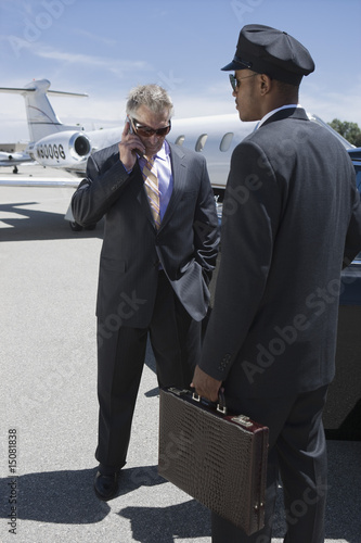 Senior businessman standing outside private jet and talking on phone, Chauffeur holding his suitcase.