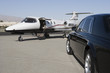 Limousine and private jet on landing strip.