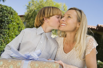 Boy kissing his mother on cheek and giving her birthday present