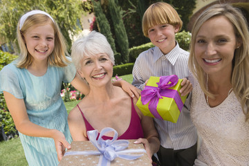 Grandmother with daughter and grandchildren in garden holding birthday present