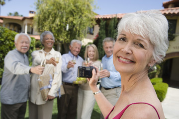Senior woman photographing friends in garden while raising toast