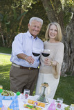 Senior couple raising toast while birthday party in garden