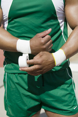 Male shot putter wrapping wrist tape, mid section