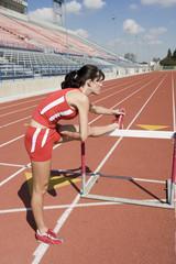 Female athlete stretching on hurdle